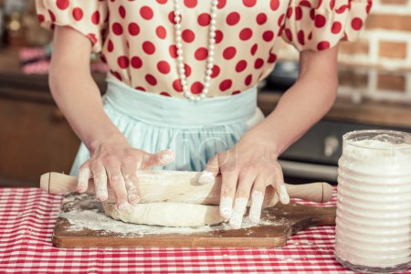 cropped shot of woman kneading dough with rolling pin at kitchen