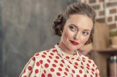 close-up portrait of beautiful adult woman in vintage polka dot shirt and pearl necklace looking away