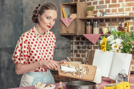 beautiful adult housewife pouring sliced mushrooms into baking trey for cake and looking at camera at kitchen