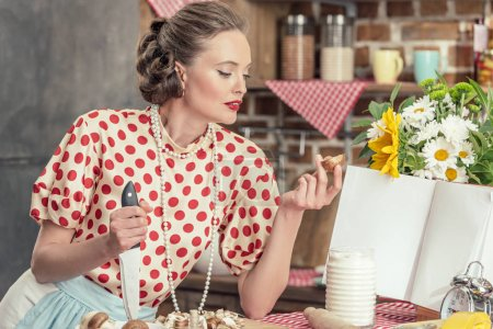 beautiful adult housewife with knife looking at sliced mushroom while cooking at kitchen