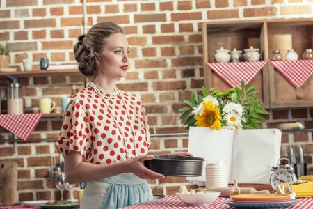 beautiful adult housewife with baking trey for cake looking away at kitchen