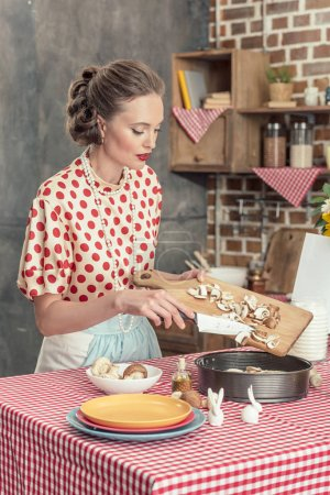 Photo for Beautiful adult housewife pouring sliced mushrooms into baking trey for cake at kitchen - Royalty Free Image