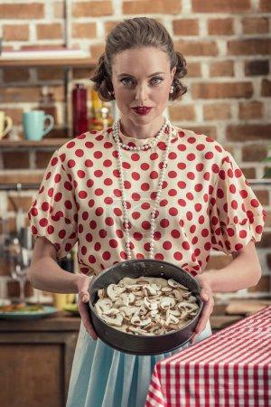 beautiful adult housewife in polka dot shirt with trey of mushrooms looking at camera at kitchen