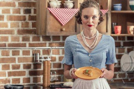 Photo pour Attrayant adulte ménagère avec gâteau fraîchement cuit en regardant la caméra à la cuisine - image libre de droit