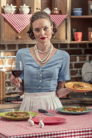 beautiful adult housewife with glass of red wine and freshly baked cake at kitchen