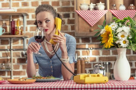 beautiful adult housewife with glass of wine talking by vintage rotary phone at kitchen