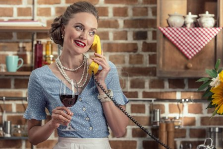 attractive adult housewife with glass of wine talking by vintage rotary phone at kitchen