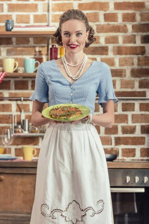 happy adult housewife in vintage clothes holding plate with mushroom cake at kitchen