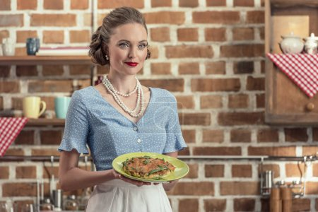 smiling adult housewife in vintage clothes holding plate with mushroom cake at kitchen