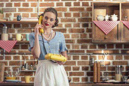 attractive adult housewife talking by vintage rotary phone at kitchen