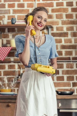 beautiful happy housewife talking by vintage rotary phone at kitchen