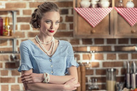 confident adult housewife in vintage clothes standing at kitchen and looking away