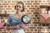 attractive adult housewife with fryin pan looking at camera at kitchen