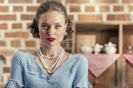 attractive adult housewife looking at camera at kitchen