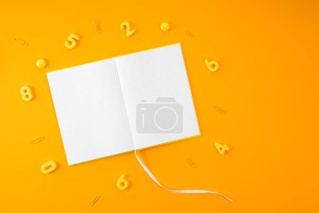 top view of blank notebook surrounded with digits and paper clips on yellow