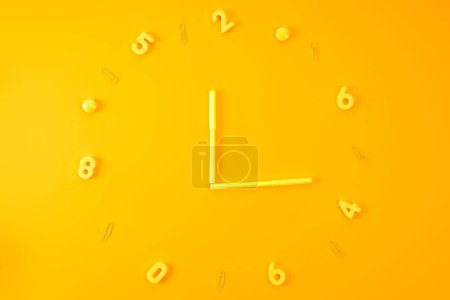 Photo for Top view of watch made of markers, plastic digits and paper clips on yellow - Royalty Free Image