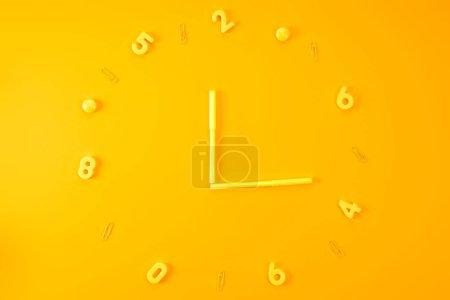 Photo pour Vue de dessus de montre fait des marqueurs, des chiffres en plastique et des trombones sur jaune - image libre de droit