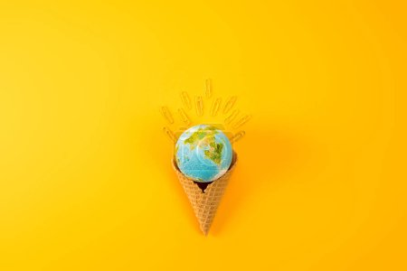 top view of earth globe in waffle cone with paper clips on yellow