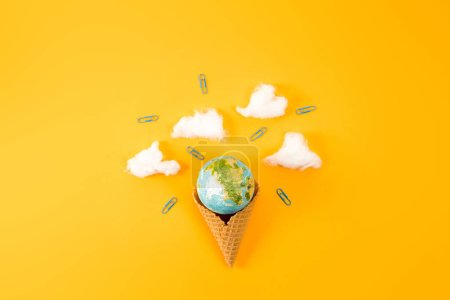 top view of earth globe in waffle cone with clouds made of cotton on yellow
