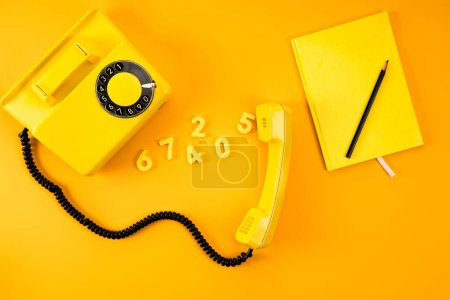 top view of vintage phone with notebook and numbers on yellow
