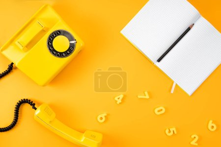 top view of vintage phone with blank notebook and numbers on yellow