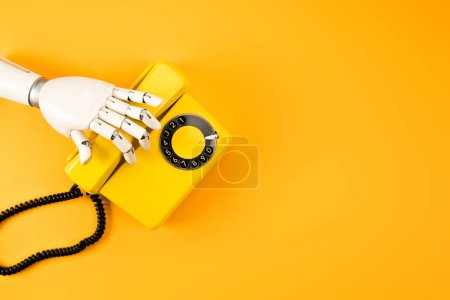 Photo for Cropped shot of robotic hand reaching for vintage phone on yellow tabletop - Royalty Free Image