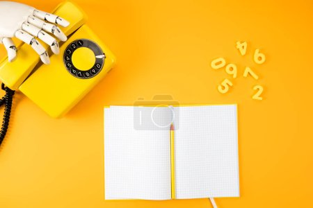 cropped shot of robotic hand reaching for vintage phone on yellow tabletop with blank notebook and math numbers