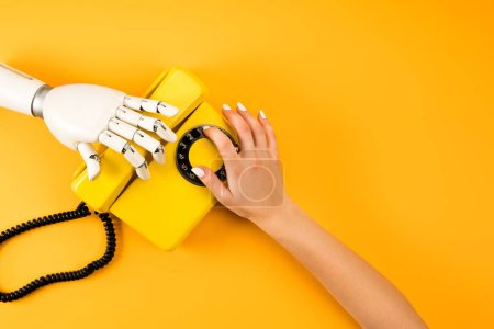 Photo for Cropped shot of woman and robot reaching for vintage phone on yellow - Royalty Free Image