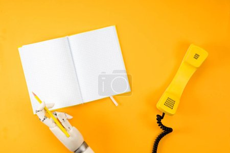 cropped shot of robotic hand writing in blank notebook on yellow tabletop with vintage phone