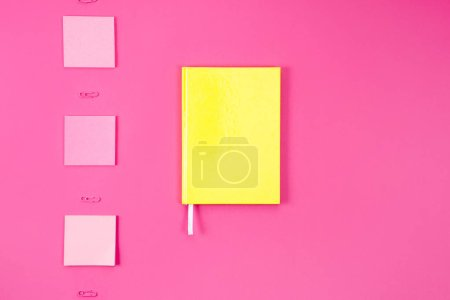 flat lay with yellow notebook with stickers and paper clips on pink