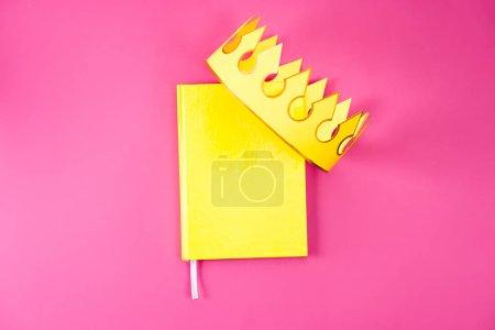 Photo pour Vue de dessus du cahier jaune avec Couronne de papier rose - image libre de droit