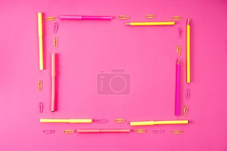 top view of frame made of pencils, markers and paper clips on pink