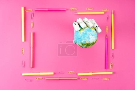 top view of robotic hand holding globe inside of frame made of pencils and markers on pink
