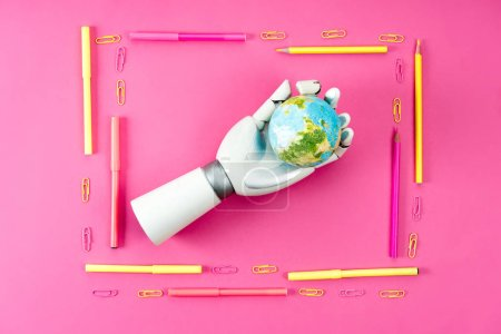 Photo for Top view of robotic hand holding earth globe inside of frame made of pencils and markers on pink - Royalty Free Image