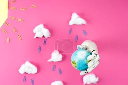top view of rain composition arranged of paper clips and cotton with robotic hand holding earth globe on pink