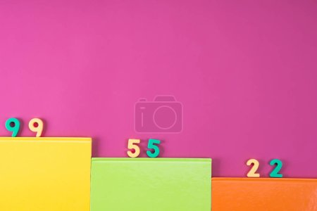 top view of colorful notebooks and math education numbers on pink