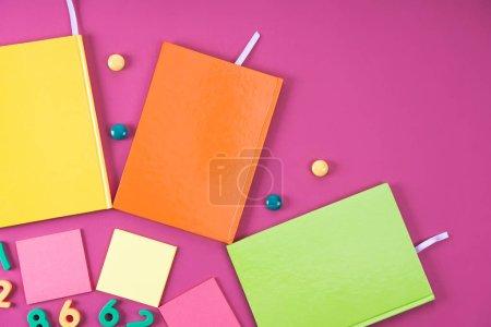 Photo pour Plat posé avec des carnets colorés et des appareils sur rose - image libre de droit