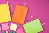 flat lay with colorful notebooks and appliances on pink