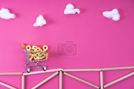 shopping cart with numbers riding on bridge arranged with color pencils on pink