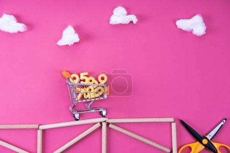 Photo pour Panier avec divers numéros chevauchant sur le pont arrangé avec des crayons de couleur aux ciseaux sur rose - image libre de droit