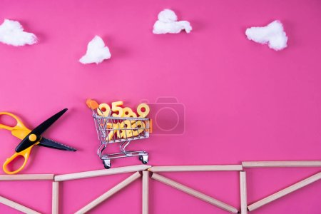 shopping cart with various numbers riding from scissors on bridge arranged with color pencils on pink