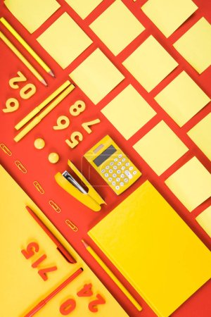 top view of arranged yellow schooling supplies on red