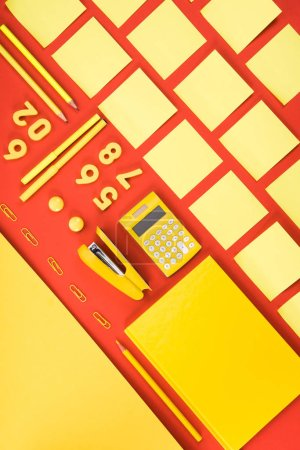 flat lay with arranged yellow schooling supplies in rows on red