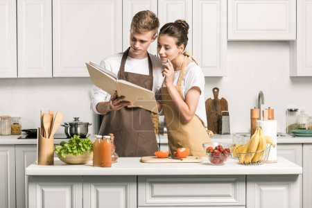 young couple cooking salad and looking at cookbook in kitchen