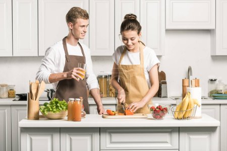 Photo for Young couple cooking salad and cutting vegetables in kitchen - Royalty Free Image