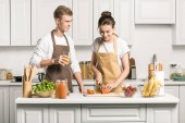 young couple cooking salad and cutting vegetables in kitchen