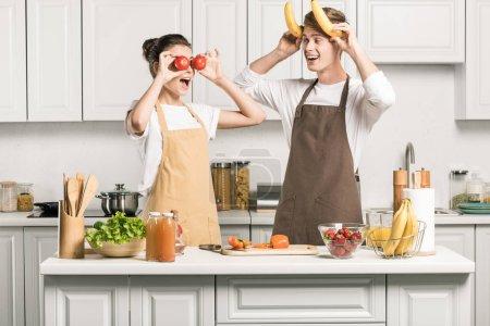 Foto de Joven pareja teniendo diversión con plátanos y tomates en la cocina - Imagen libre de derechos