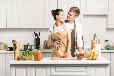 Photo for Boyfriend hugging girlfriend while she cooking salad in kitchen - Royalty Free Image