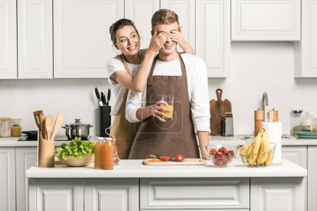 Photo for Girlfriend closing eyes for boyfriend while he cooking salad in kitchen - Royalty Free Image