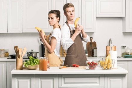 young couple having fun and holding banana guns in kitchen